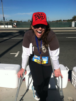 Aurora giving a big open mouth smile while leaning on her crutches after the Surf City half marathon 2012