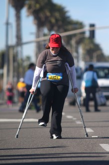 Aurora looks down while moving on crutches at the Surf City Half Marathon 2012