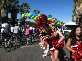 Cheerleaders cheering by a big balloon banner at the Tour de Palm Springs 2012