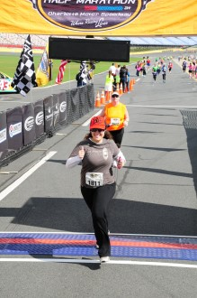 Aurora smiling as she runs underneath the finish line of the North Carolina half marathon 2012