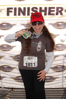 Aurora De Lucia smiling in the finisher area with her huge North Carolina half marathon medal 2012