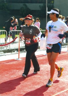runners Joe and Aurora on the red carpet finish of the Hollywood Half Marathon 2012, smiling a bit while coming in
