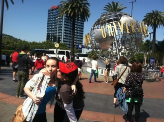 Aurora kissing her friend Amber on the cheek in front of the Universal Studios Hollywood ball