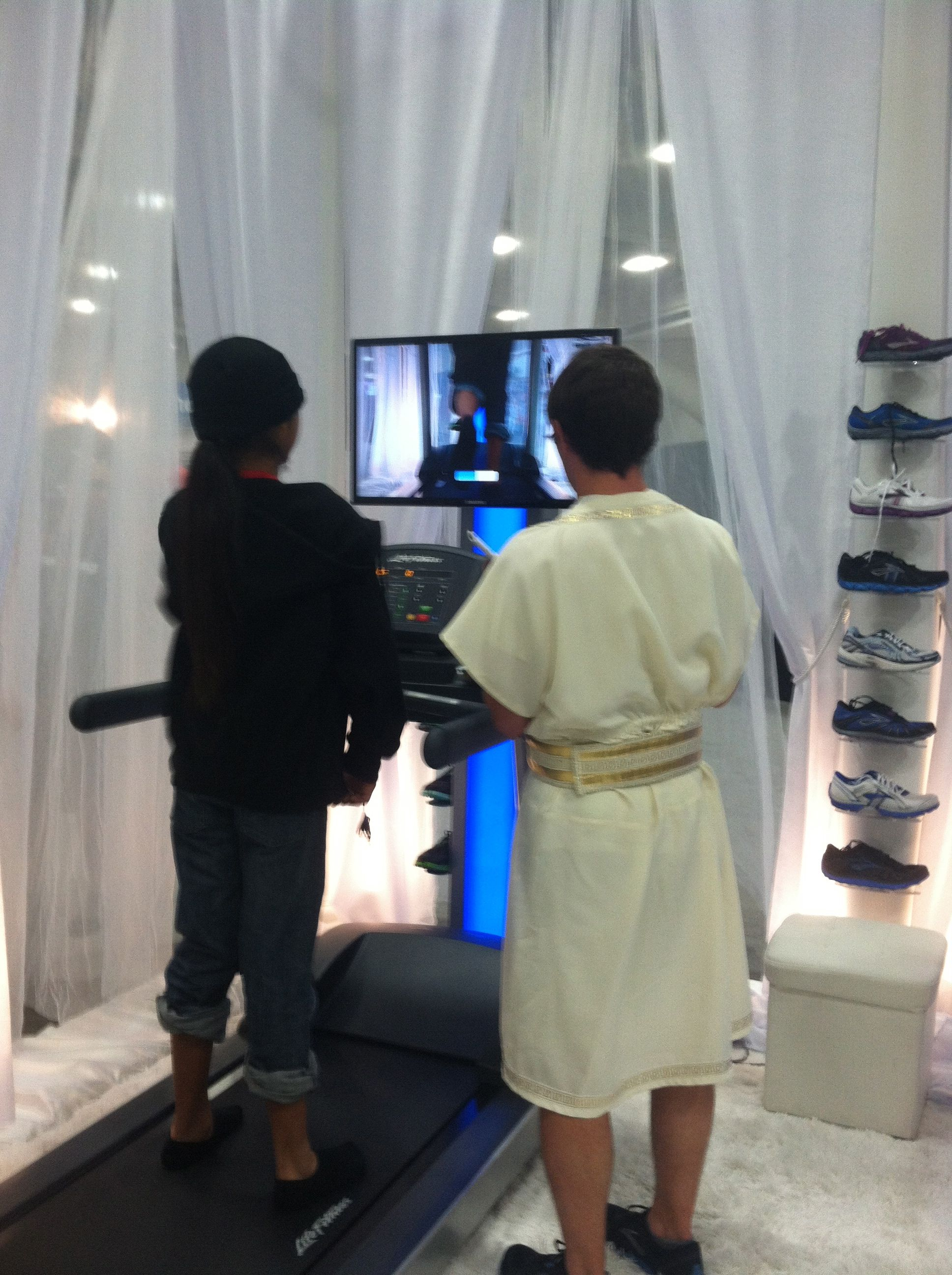 an unexpected friend from high school in a toga evaluating someone's form at the Brooks heaven display at the Rock n Roll San Diego marathon expo booth 2012