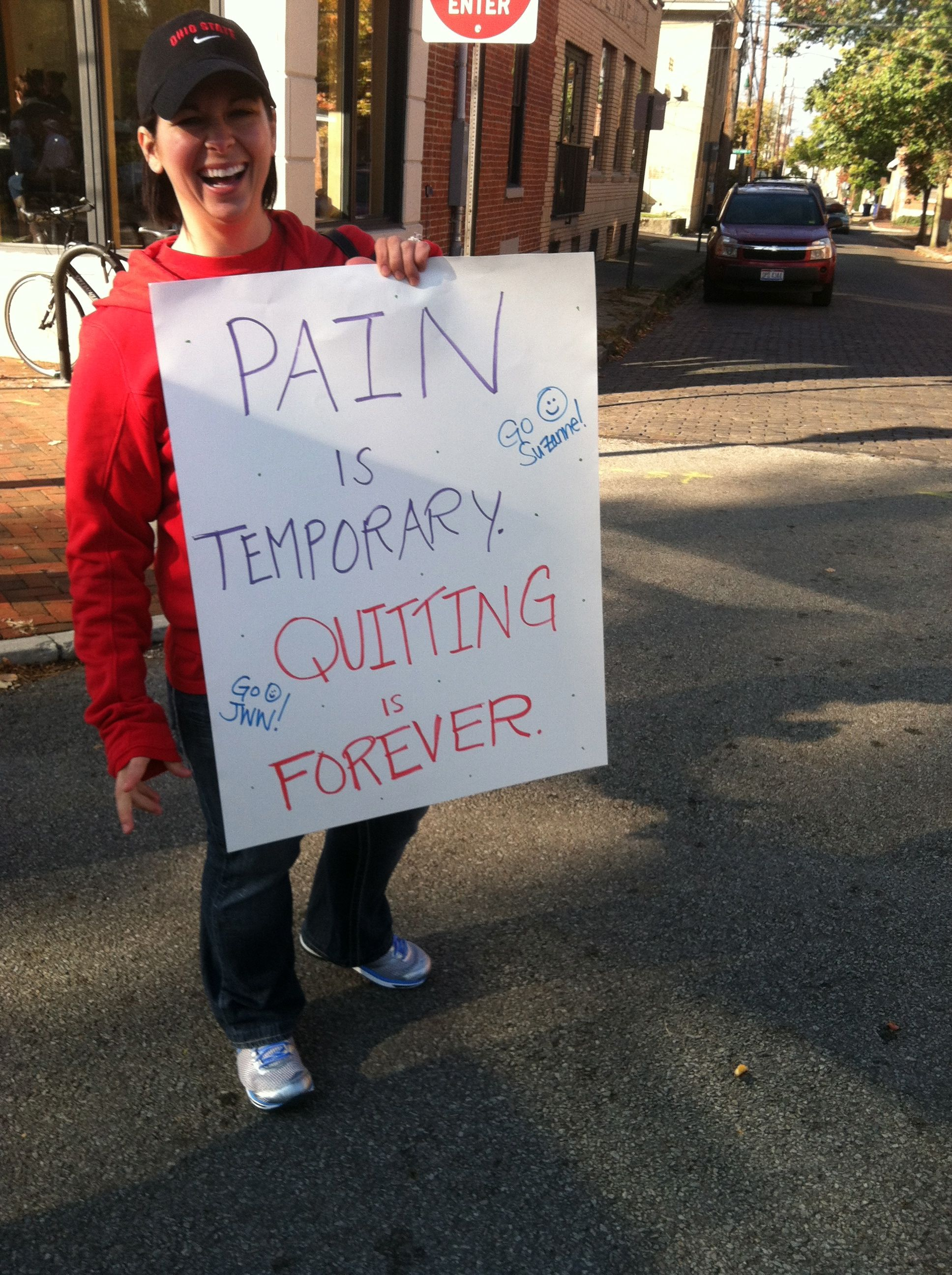 "a spectator at the Nationwide Children's Hospital Columbus Half Marathon 2012 holding a sign that says ""Pain is temporary, quitting is forever"""