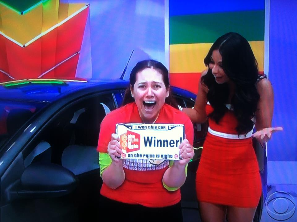 "Aurora De Lucia holding her ""winner"" license plate after she won the car on The Price is Right"