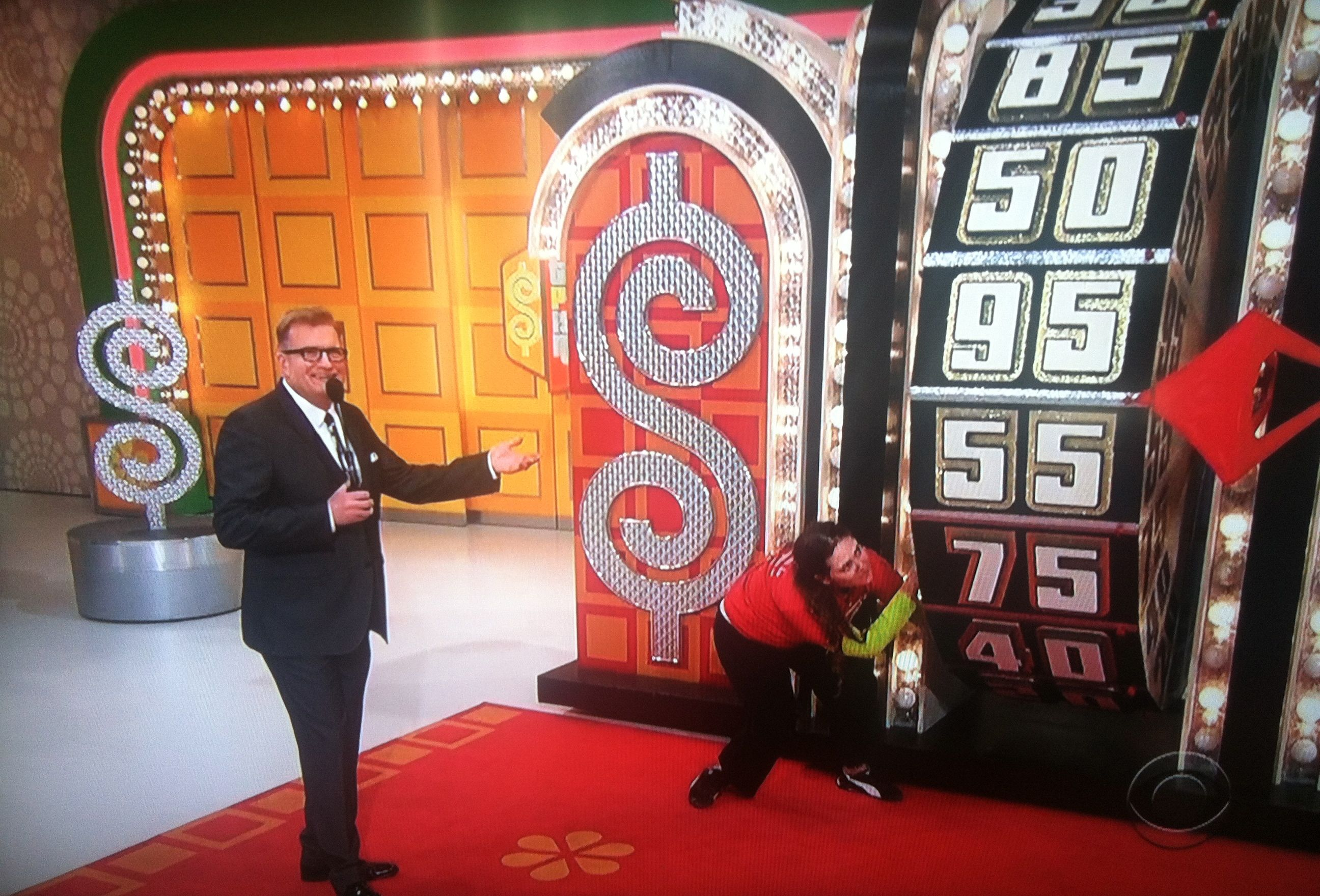 Aurora De Lucia down low, getting momentum on The Price is Right wheel as Drew Carey talks.