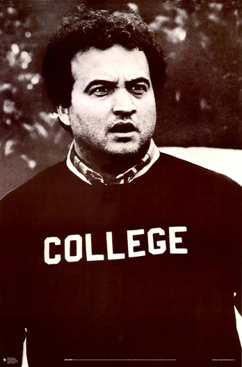 Jim Belushi wearing a college sweatshirt, making a confused face