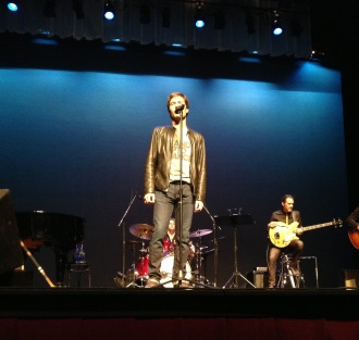 Eric McCormack onstage in a Stand Up 2 Cancer shirt, singing a song at his concert