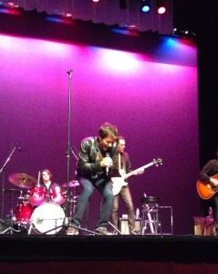 "Eric McCormack leaning down and singing earnestly during his concert ""The Concert I Never Gave..."" at the El Portal Theatre."