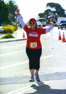 Aurora running in a red shirt with her hands up on a fairly empty street at Run Montecito-Summerland
