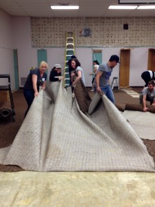 Aurora and her group from the Do Good Bus pulling up carpet during a renovation