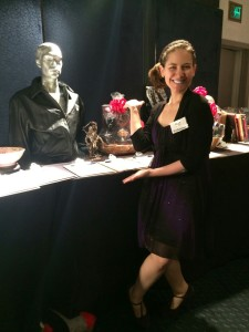 Aurora posing with some silent auction materials at APLA STAGE event
