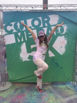 Aurora De Lucia stands on one foot on her toes, posing at the Color Me Rad sign