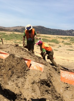 Aurora De Lucia being guided up a little muddy hill during the Irvine Lake Summer of Mud run 2014