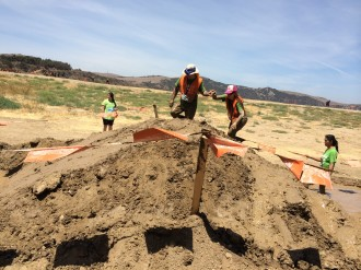 Aurora being led up the side of a mud mountain at the Irvine Lake Mud Run 2014