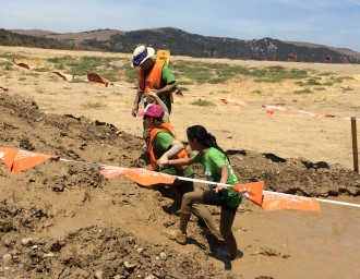 Aurora getting pulled out of mud by her guides at the Irvine Lake Obstacle Course Mud Run 2014