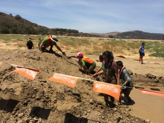 Aurora reaching up to her guide in the mud at the Irvine Lake Mud Rud 2014