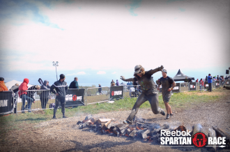 Aurora jumping over fire at the end of the Beast at Spartan Ohio trifecta-in-a-day 2014