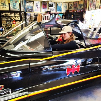 Aurora De Lucia sitting in the Batmobile, talking on the Bat Phone