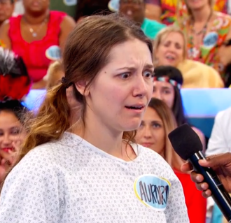 Aurora De Lucia giving crazy eyes, looking down, with a microphone pointed at her on Let's Make a Deal