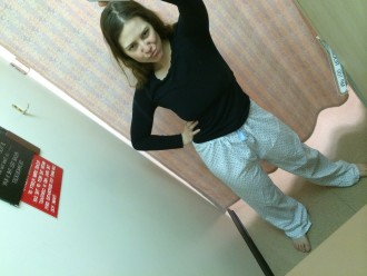 Aurora De Lucia trying to give a tough girl post in the mirror wearing her hospital pants