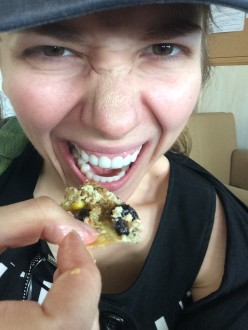 Aurora De Lucia smiling while stuffing her face with nachos