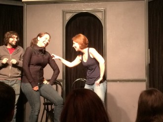 Aurora and her partner making silly faces and laughing during improv with The Deltones at iO west