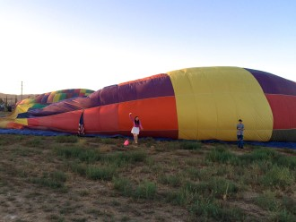 Aurora standing at the side of an inflating hot air balloon