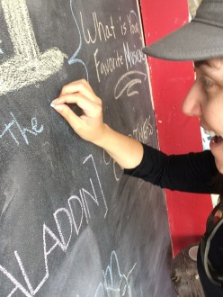 Aurora writing her favorite musical on the board at the Samuel French Bookshop