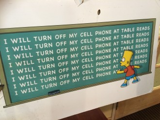 "Bart Simpson writing ""I will turn off my cell phone at the table read"" on a chakboard on a sign on the Fox lot at The Simpsons table read"