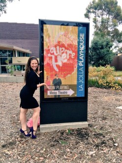 Aurora De Lucia in front of the Up Here sign at La Jolla playhouse