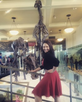 aurora smiling in front of a dinosaur at the AMNH filtered