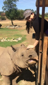 Aurora smiling petting the rhinos horn